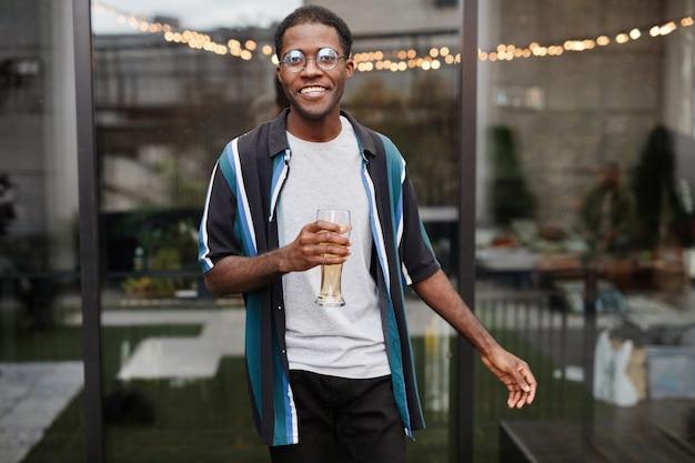 Taillenporträt eines jungen afroamerikanischen mannes, der ein getränk hält, während er eine party im freien auf dem dach genießt, platz kopieren