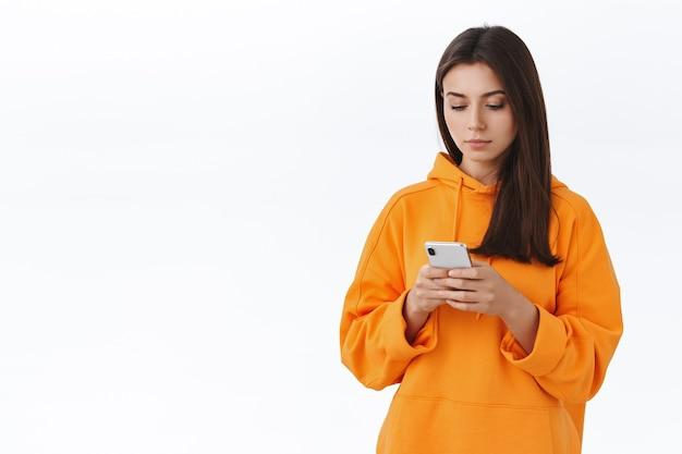 Taillenporträt eines jungen attraktiven hipster-mädchens in orangefarbenem hoodie mit mobiltelefon, blick auf das smartphone-display mit ernstem gesicht, nachricht schreiben, freund sms schreiben oder foto bearbeiten, um es online zu veröffentlichen