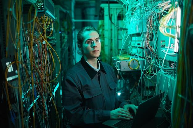 Taillenporträt eines jungen netzwerktechnikers, der die kamera im serverraum anschaut, während er den supercomputer im rechenzentrum einrichtet