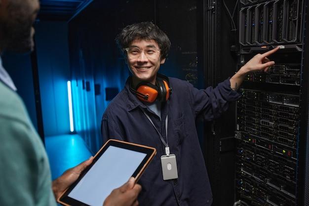 Taillenporträt eines lächelnden asiatischen mannes, der kollegen anschaut, während er supercomputerserver im rechenzentrum einrichtet, platz kopieren
