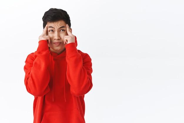Taillenporträt eines unruhigen jungen intensiven asiatischen mannes kann keinen schminkplan machen, denken unter druck, tempel berühren, schielen und stirnrunzeln schauen verwirrt, denken, versuchen, sich auf die aufgabe zu konzentrieren, weiße wand.