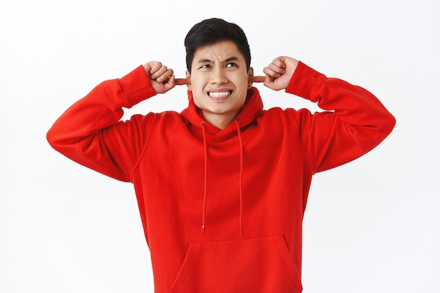 Taillenporträt eines verärgerten jungen mannes, asiatischer männlicher student, der sich über laute nachbarn beschwert, ohren schließen und eine grimasse verziehen, irritiert aufblicken, laute nervige musik hören, weiße wand.