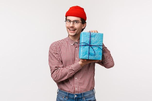 Taillenporträt freundlicher lustiger süßer mann kaufte geschenk für seinen kumpel, hielt verpacktes geschenk und lächelte, kaufte überraschungsgeschenk als zur b-tagesparty gehend, in der roten mütze