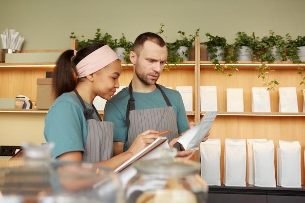 Taillenporträt von zwei jungen kellnern, die schürzen tragen, während sie inventar im café oder café machen, platz kopieren
