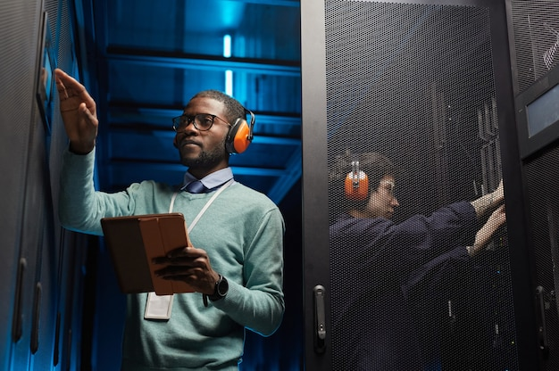 Taillenporträt von zwei technikern, die ein computernetzwerk einrichten, während sie im rechenzentrum arbeiten