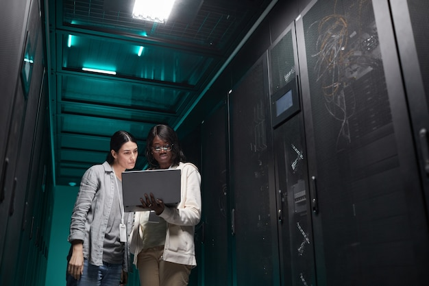 Taillenporträt von zwei weiblichen it-ingenieuren, die ein servernetzwerk über einen laptop einrichten, während sie im rechenzentrum arbeiten, platz kopieren