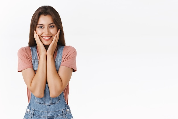 Taillenporträt weiblich, süße und glückliche lächelnde frau, die reine, saubere haut berührt und erfreut grinst, als sie hautunreinheiten und akne losgeworden ist, sich wiedererlebt und schön fühlt, weißer hintergrund steht