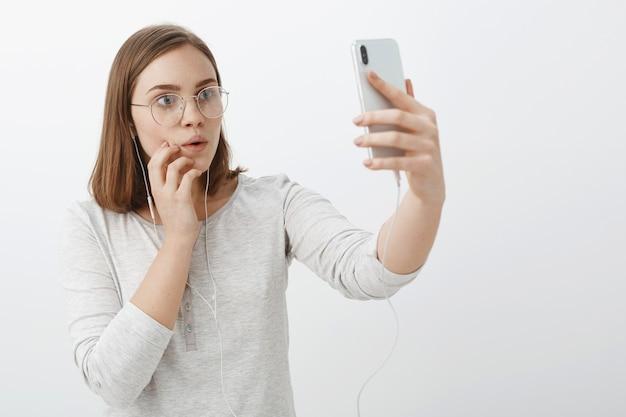 Taillenschuss der kreativen neugierigen und unterhaltenen bezaubernden frau in der brille, die kopfhörer trägt, die hand heben, während smartphone fasziniert und interessiert auf gerätebildschirm schaut, der erstaunliches video anschaut