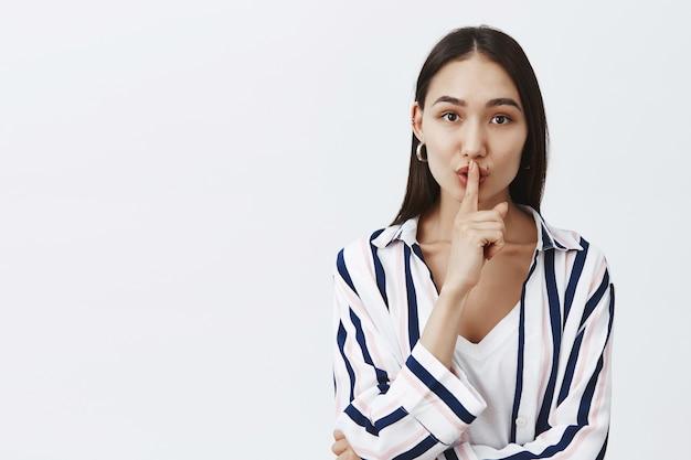Taillenschuss der modischen attraktiven frau in der gestreiften bluse, die lippen faltet und shhh sagt, während shush-geste mit zeigefinger über mund macht, geheim hält oder gerüchte erzählt