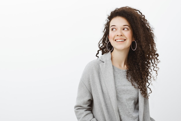 Taillenschuss der sorglosen glücklichen europäischen unternehmerin in ohrringen und im stilvollen mantel, mit breitem freudigem lächeln nach links schauend