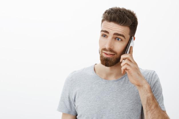 Taillenschuss des ehrgeizigen gutaussehenden beschäftigten mannes mit bart, schnurrbart und blauen augen, die ernst und entschlossen schauen, geschäft über smartphone zu besprechen, das handy nahe ohr gegen graue wand hält