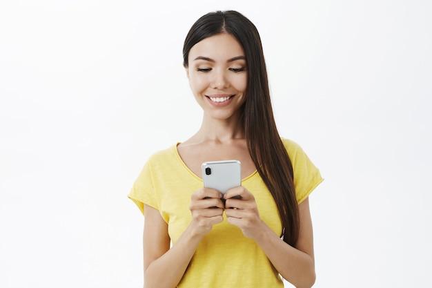 Taillenschuss des entzückten sorglosen attraktiven weiblichen mitarbeiters im gelben trendigen t-shirt, das smartphone hält, das auf telefonbildschirm schaut