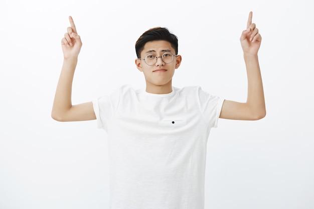Taillenschuss des gewöhnlichen hübschen jungen asiatischen jungen in den runden gläsern, die hände zeigen, die nach oben zeigen