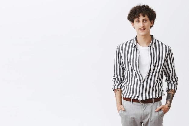 Taillenschuss des stilvollen modernen jungen hipster-mannes im gestreiften hemd und in der grauen hose, die hände in den taschen mit dunklem lockigem haar des schnurrbartes und tätowierungen halten, die sich für datum über graue wand verkleiden