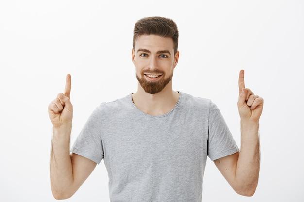 Taillenschuss eines gutaussehenden selbstbewussten männlichen unternehmers mit bart und brauner frisur, der die zeigefinger anhebt und mit einem selbstbewussten, entzückten blick nach oben zeigt, um sicherzustellen, dass sein produkt über der weißen wand großartig ist