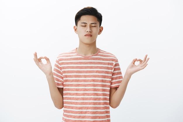 Taillenschuss eines ruhigen, fokussierten, attraktiven asiatischen männlichen studenten, der die kontrolle über die gedanken übernimmt, in lotus-pose mit zen-geste steht und meditiert, um mit yoga energie wiederherzustellen