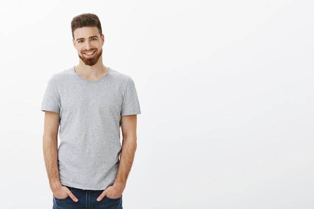 Taillenschuss eines sorglosen, ehrgeizigen und gutaussehenden bärtigen mannes mit schnurrbart und blauen augen, der hände in jeanstaschen hält, die mit perfekten weißen zähnen mit sicherem ausdruck über grauer wand lächeln