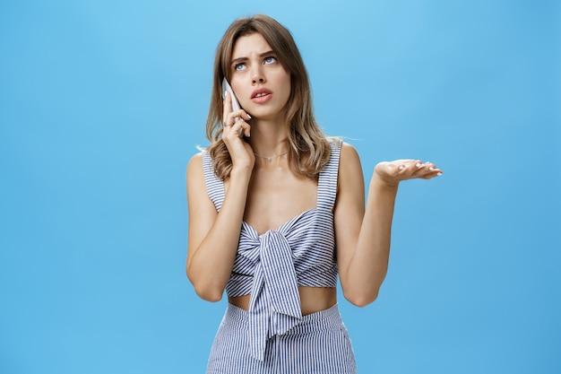 Taillenschuss von verwirrter und verwirrter süßer freundin im passenden outfit, die schulter zucken und handfläche in ahnungsloser geste heben, die beim telefonieren nach oben schaut
