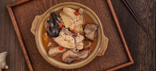 Taiwanesisches essen - hausgemachte köstliche sesamöl-hühnersuppe in einer schüssel auf dunklem holztischhintergrund.