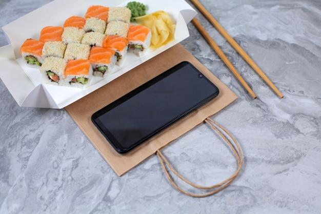 Takeaway-box mit sushi-rollen und smartphone auf brauner papiertüte