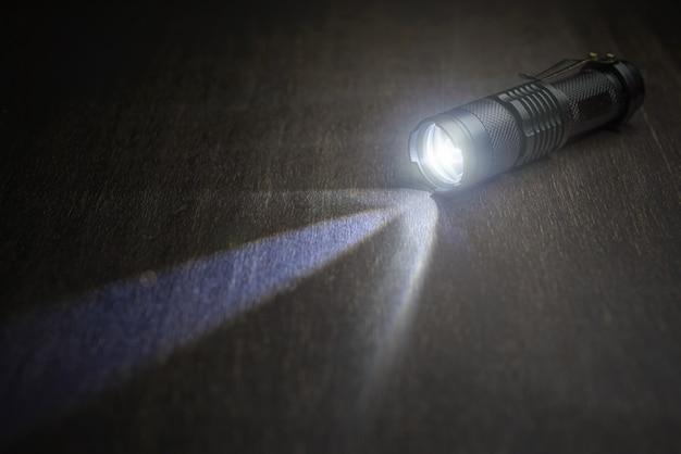 Taktische wasserdichte taschenlampe. led-taschenlampe leuchtet auf dem tisch in rauch..