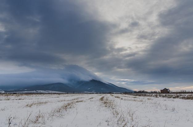 Tal mit schnee bedeckt unter dem dunklen bewölkten himmel