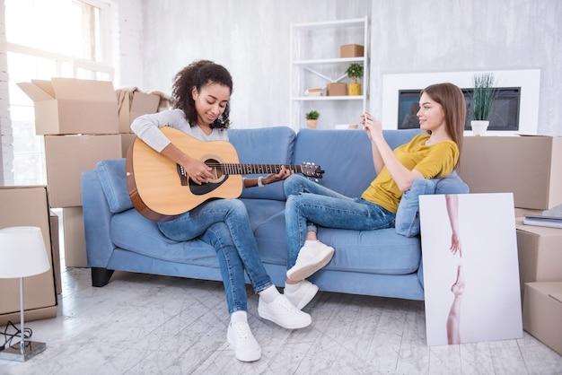 Talent schätzen. charmantes junges mädchen, das neben ihrer besten freundin auf der couch sitzt und ihre gitarre am telefon filmt