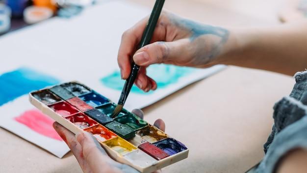 Talent und kreativität. beschnittene aufnahme der künstlerin, die abstrakte kunstwerke mit aquarell malt.