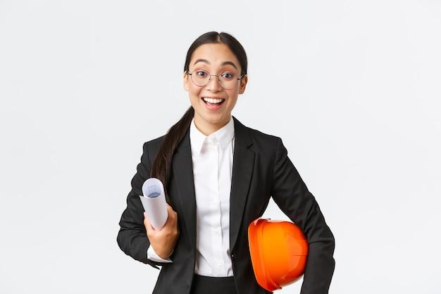Talentierte aufgeregte asiatische architektin, die mit den bauarbeiten beginnt, blaupausen und schutzhelm hält, business-anzug trägt, ingenieure im baubereich trifft, glücklich lächelt, weißer hintergrund