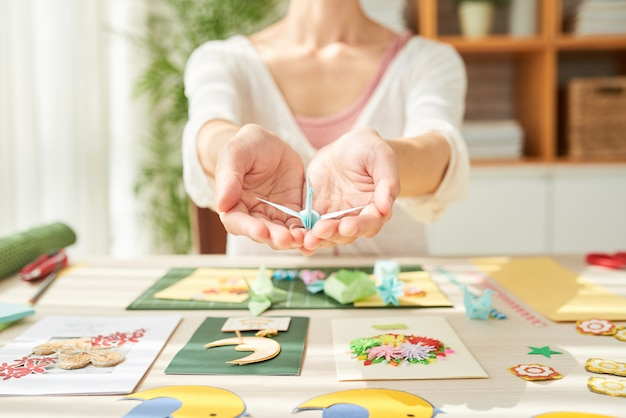 Talentierte handwerkerin mit origami-kranich