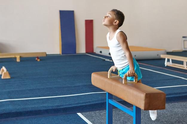 Talentierter fleißiger afrikanischer junge, der drinnen im fitnessstudio trainiert
