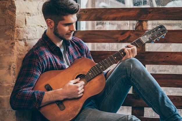 Talentierter gitarrist. schöner junger mann, der gitarre spielt, während er auf der fensterbank sitzt