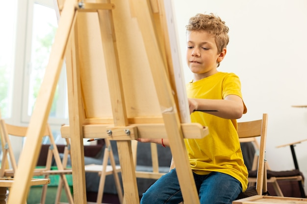 Talentierter junge, der sich beim malen in der kunstschule gut fühlt