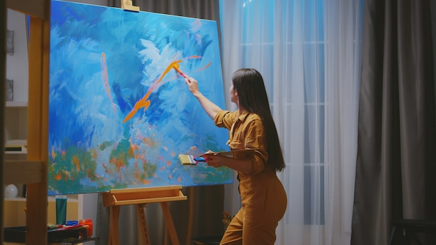 Talentierter junger maler, der verschiedene farben auf leinwand verwendet.