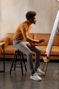 Talentierter junger mann, der die leinwand betrachtet, während er ein meisterwerk schafft