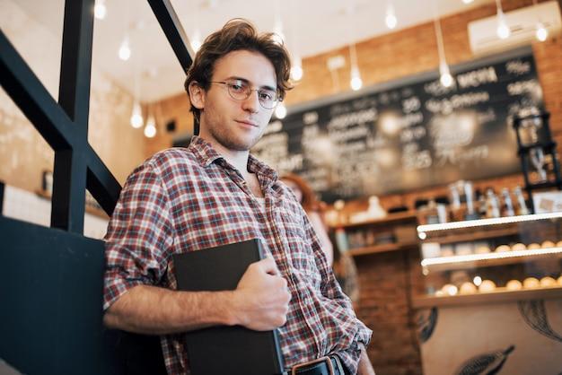 Talentierter junger mann im freizeithemd, der ein notizbuch in einem café hält.