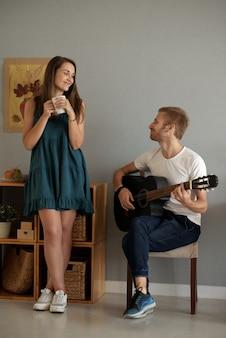 Talentierter kreativer junger mann, der gitarre für seine freundin spielt, die eine tasse tee oder kaffee trinkt