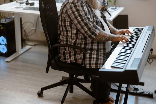 Talentierter mann mit übergewicht spielt sound-synthesizer im heimstudio