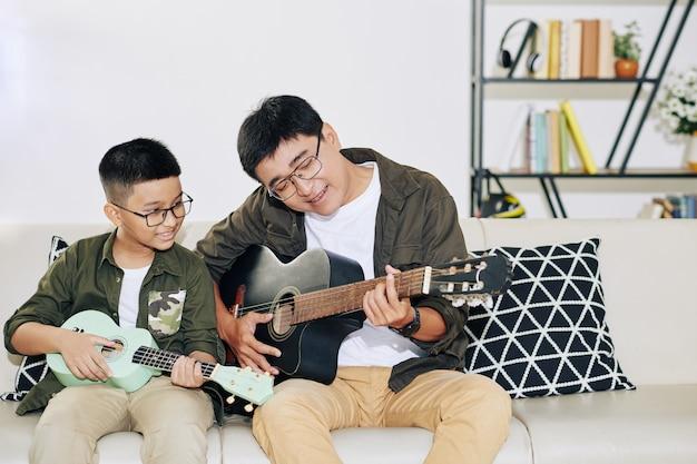 Talentierter vietnamesischer jugendlicher junge mit ukulele, der seinen vater ansieht, der gitarre spielt und unterschreibt
