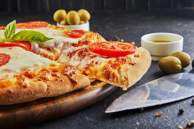 Talian pizza und zutaten zum kochen auf einem schwarzen betonhintergrund