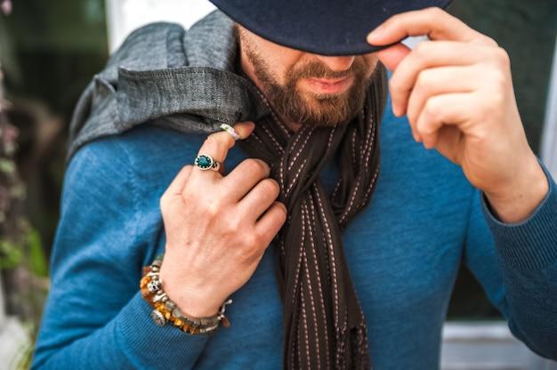 Talismane, amulette auf der hand eines mannes. ein mann in blauem pullover und schal.