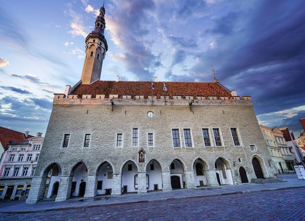 Tallinn mittelalterliches rathaus bei goldenem sonnenaufgang mit dramatischem himmel. estland.
