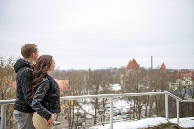 Tallinn-touristen, die lächeln und händchen halten. schönes paar, das im winter in der altstadt von tallinn spazieren geht
