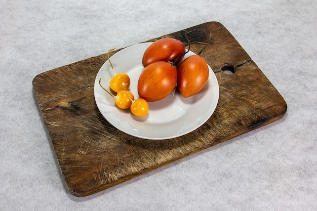 Tamarillo oder baumtomate auf holzbrett neben uvilla oder aguaymanto physalis