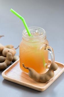 Tamarindensaft mit zucker auf grauem tisch