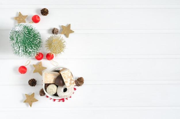 Tamburin mit weihnachtsdekorationen auf weißem holz