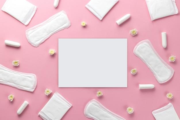 Tampons, damenbinden und leeres papier auf einem rosa hintergrund. hygienepflege an kritischen tagen. menstruationszyklus. für die gesundheit der frauen sorgen. monatlicher schutz.