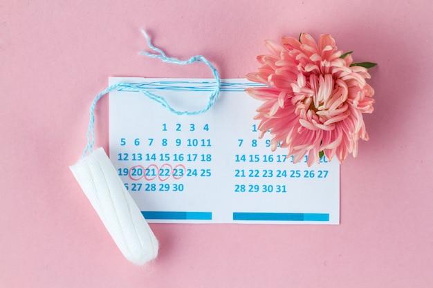 Tampons für die menstruation, frauenkalender und blumen. hygienepflege an kritischen tagen. regelmäßiger menstruationszyklus