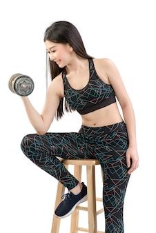 Tan skin asian fitness girl in sexy niedlichen sport-bh schwarze spandex-hose übung zum aufwärmen. üben sie die hantel-hebehaltung. durch isolierten weißen hintergrund.