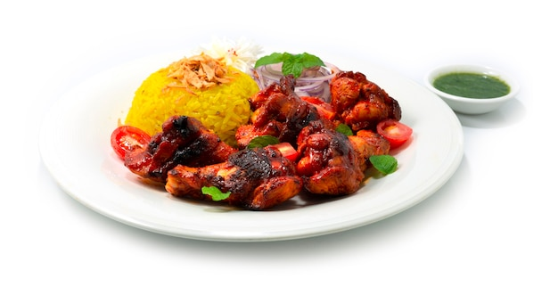 Tandoori chicken gegrillte minzsauce und biryani-reis rezept auf crispy onion ist ein klassisches indisches abendessen, das hühnerflügel in einer cremigen joghurtbasis mariniert und mit zwiebeln dekorierte gewürze vermischt